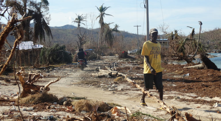 A man walks down a path in the midst of hurricane destruction