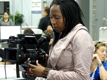 A woman stands in a room filled with people, looking into a video camera