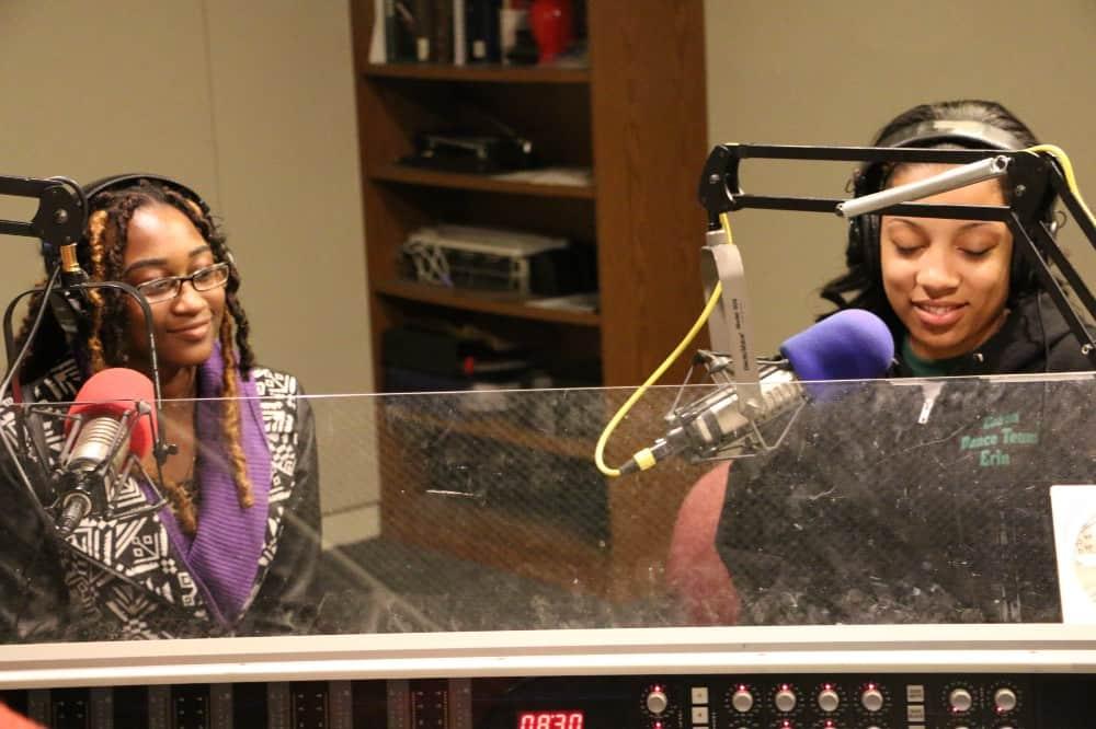 Two women sit at mics in a radio studio.
