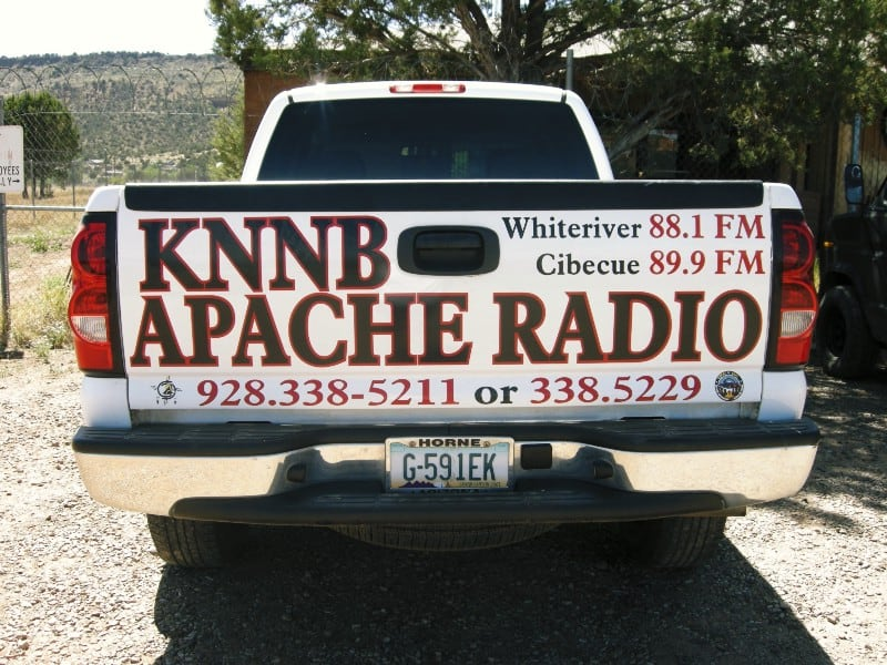 A white pickup truck with KNNB Apache Radio written on the back