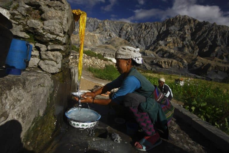 A woman washes dishes outside under a stream of water.