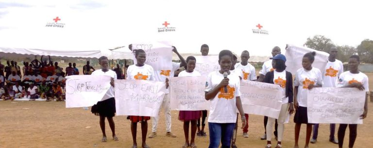 """A group of girls stand holding posters that say """"Stop early marriage"""""""
