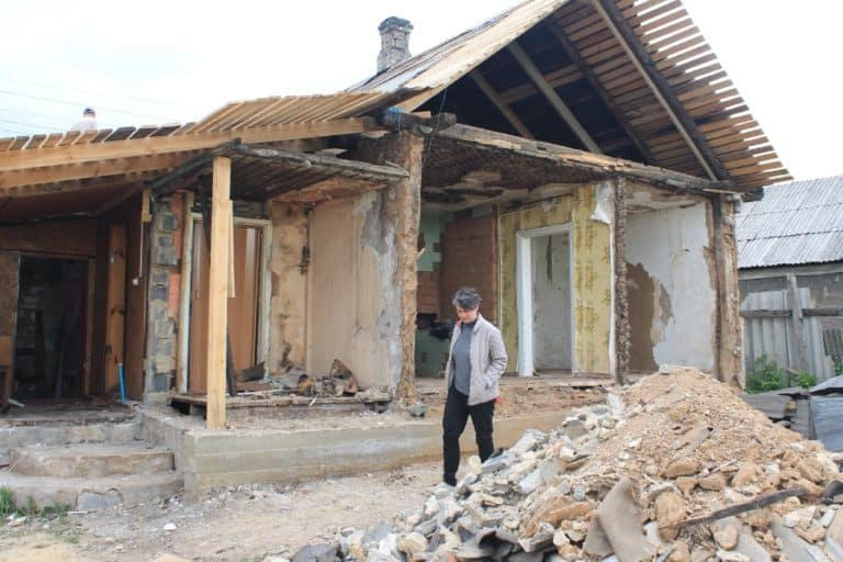 A woman walks by a building destroyed by an earthquake.