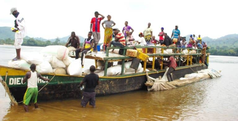 A wooden boat filled with sacks and people.