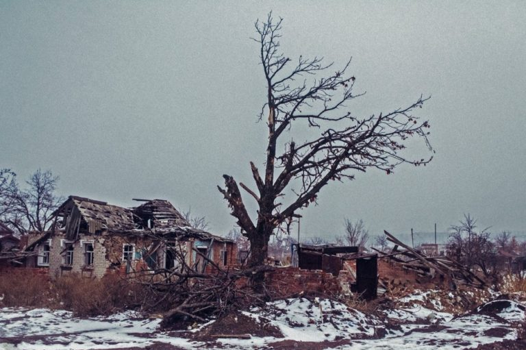 A bare tree next to a damaged house. Snow on the ground.