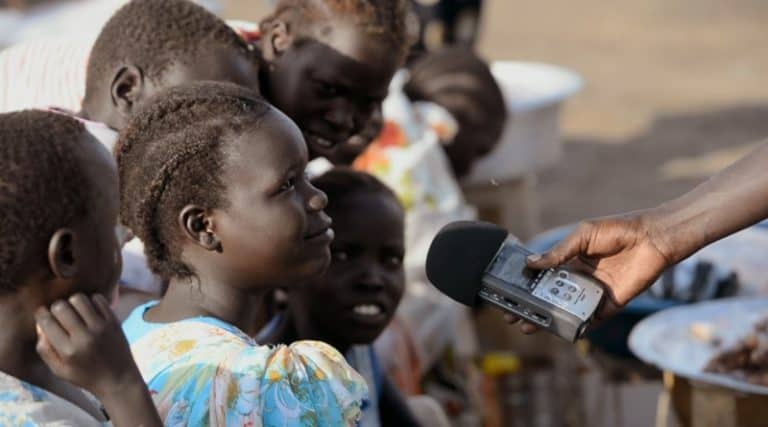 A group of children speak into a mic.