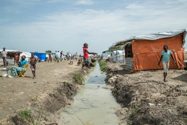Children play by a ditch with water in it that runs through a camp.