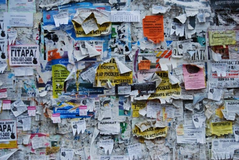 A bulletin board covered in flyers.