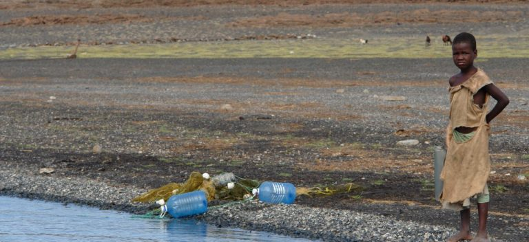 A young girl stands by a body of water; two water bottles are lying nearby.
