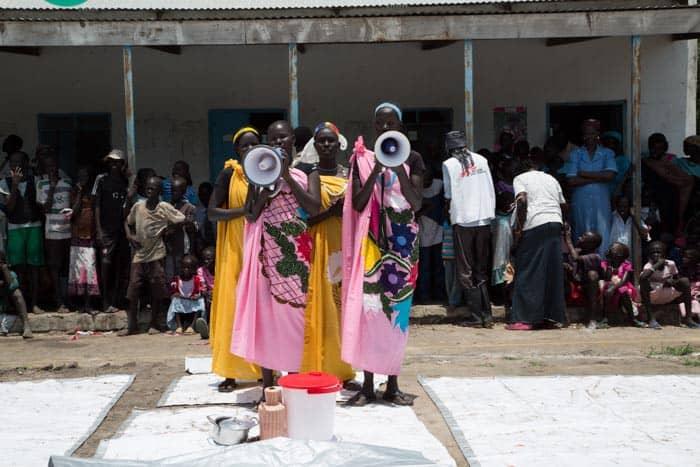 A group of four girls speak through megaphones.