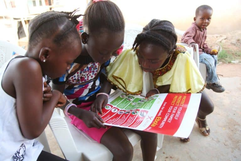 Three girls read a poster about Ebola.