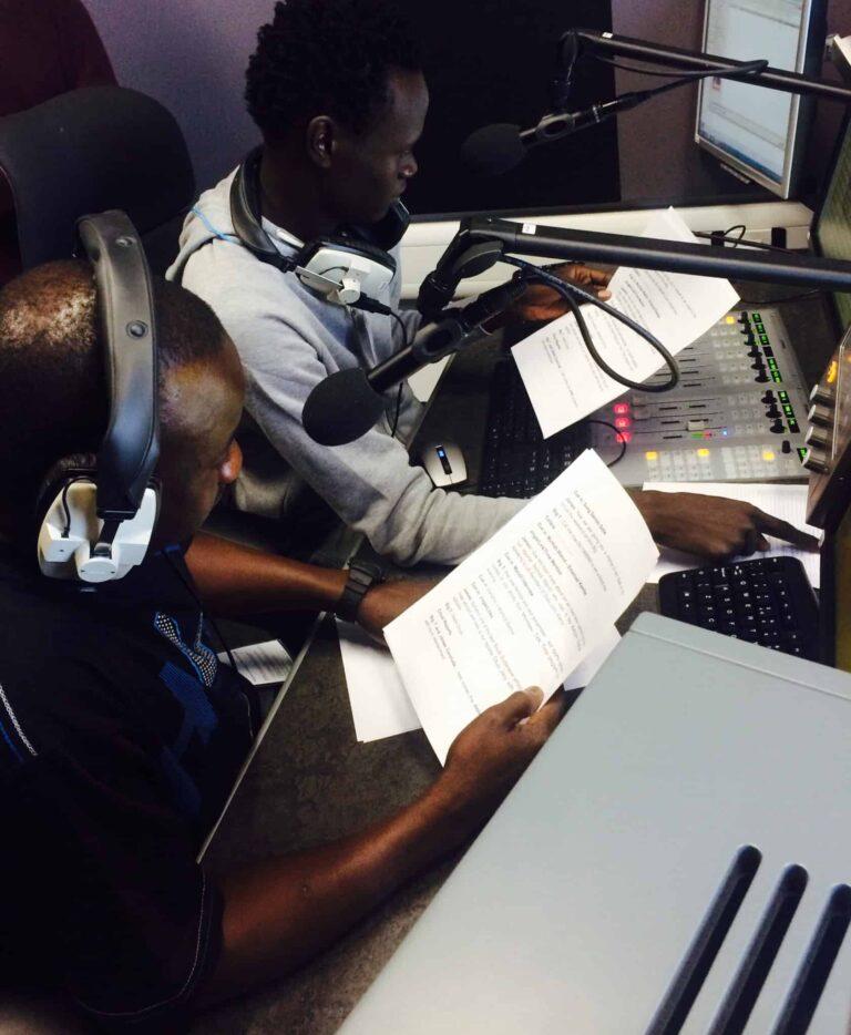 Two men sit at mics in a radio studio looking at scripts.