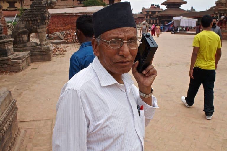 A man stands outside holding a portable radio to his ear.