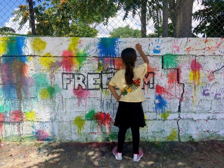 A girl writes on a concrete wall that is covered in paint splatters.