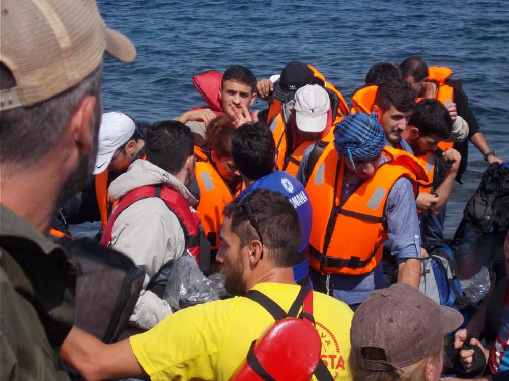 People wearing orange vests on a boat in the water.