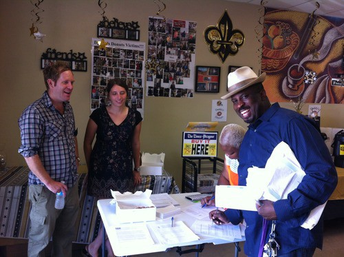 A man holds a stack of papers and fills out a form while 2 others look on