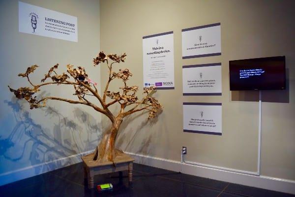 A bonsai sculpture sits in the corner of a room