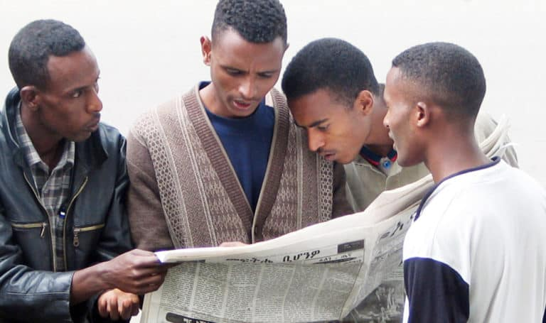 Four men stand together reading a newspaper.