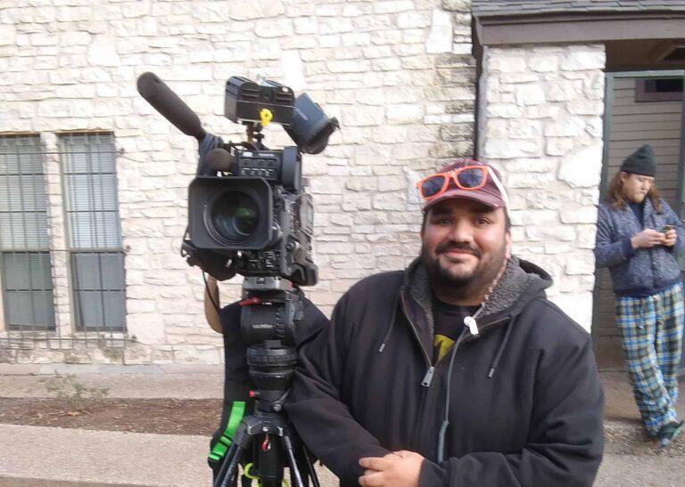 A man films outside a brick building.