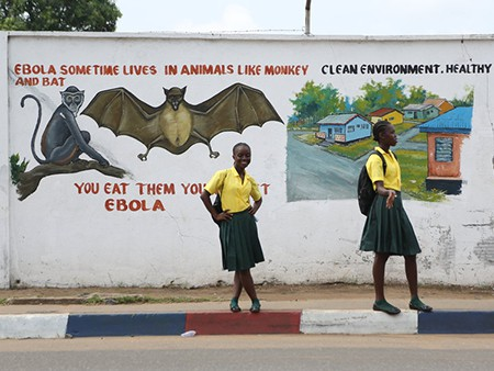 Two school girls stand on the street in front of a wall with a health message about Ebola