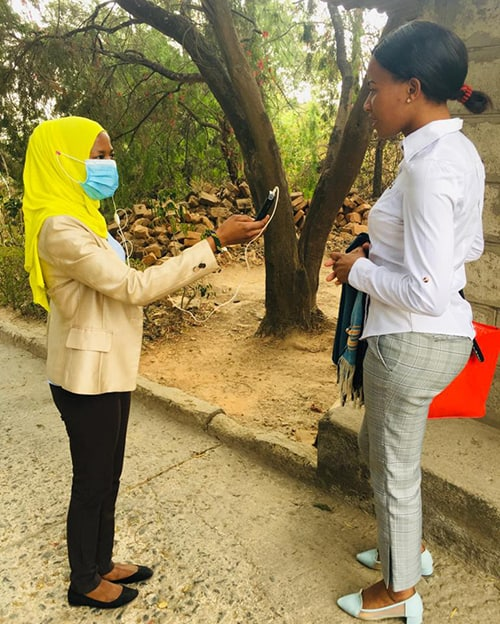 A woman wearing a mask holds a mic up to another woman, not wearing a mask