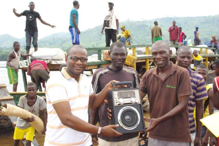 Three men stand together on a boat, holding a radio