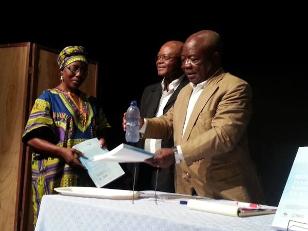 Two men, one holding a report and a woman holding a piece of paper
