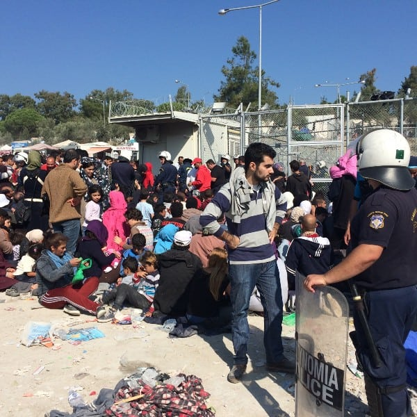 Refugees wait by a fenced area on the island