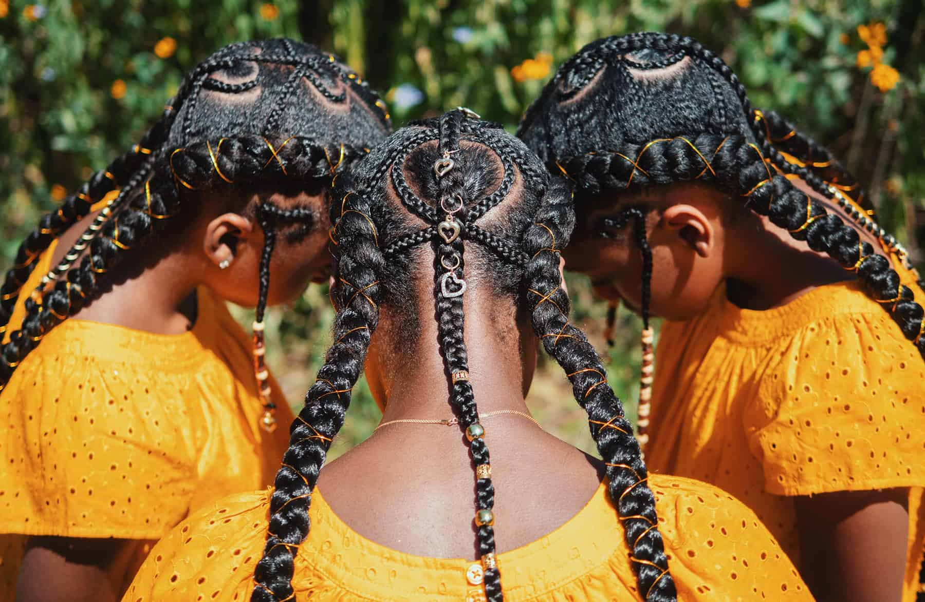 The top and back of 3 young Black women's heads are shown elaborately braided