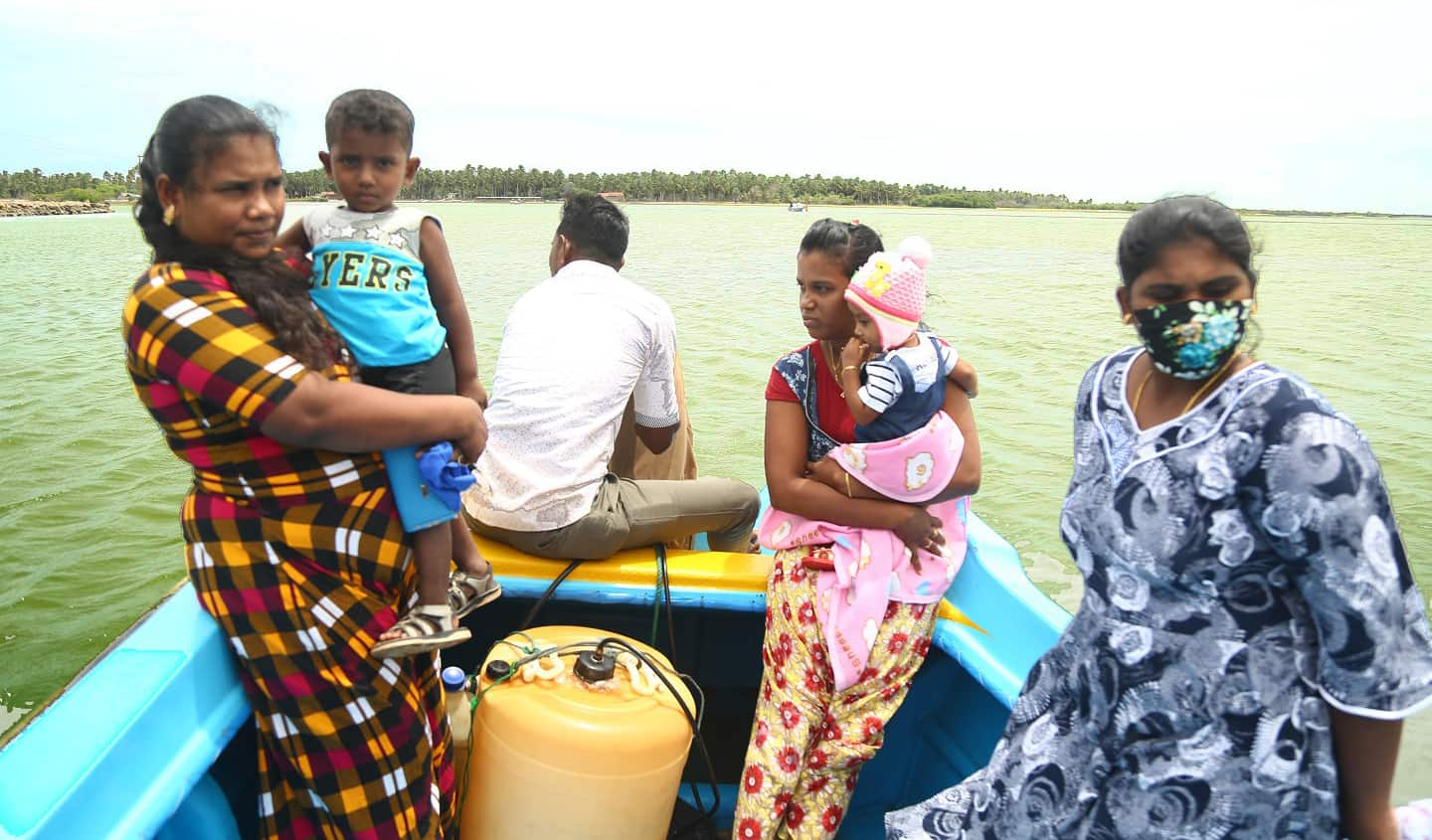 A man and three women on a small boat; two women are holding children.
