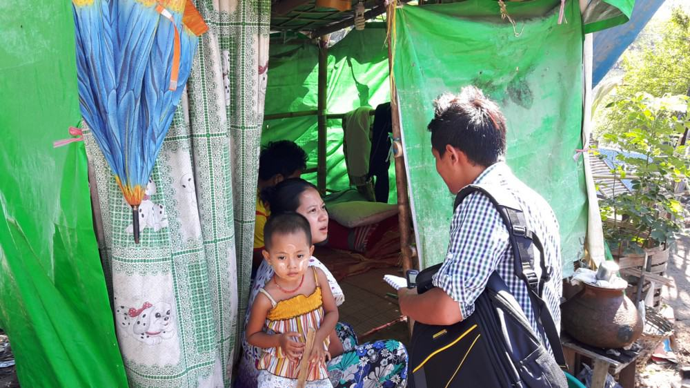 A journalist interviews a woman with a baby in a tent
