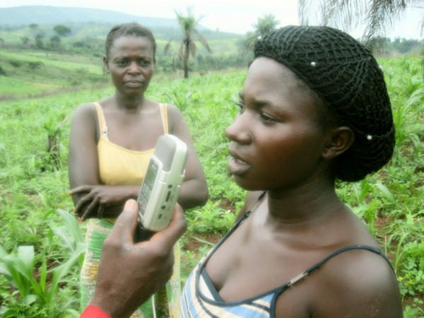 Two women stand in a field, one has a recorder held up to her face