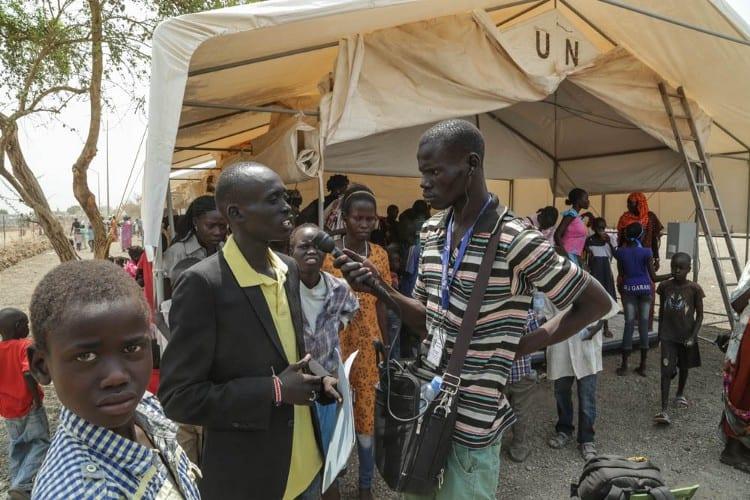 A journalist interviews a man outside a UN tent
