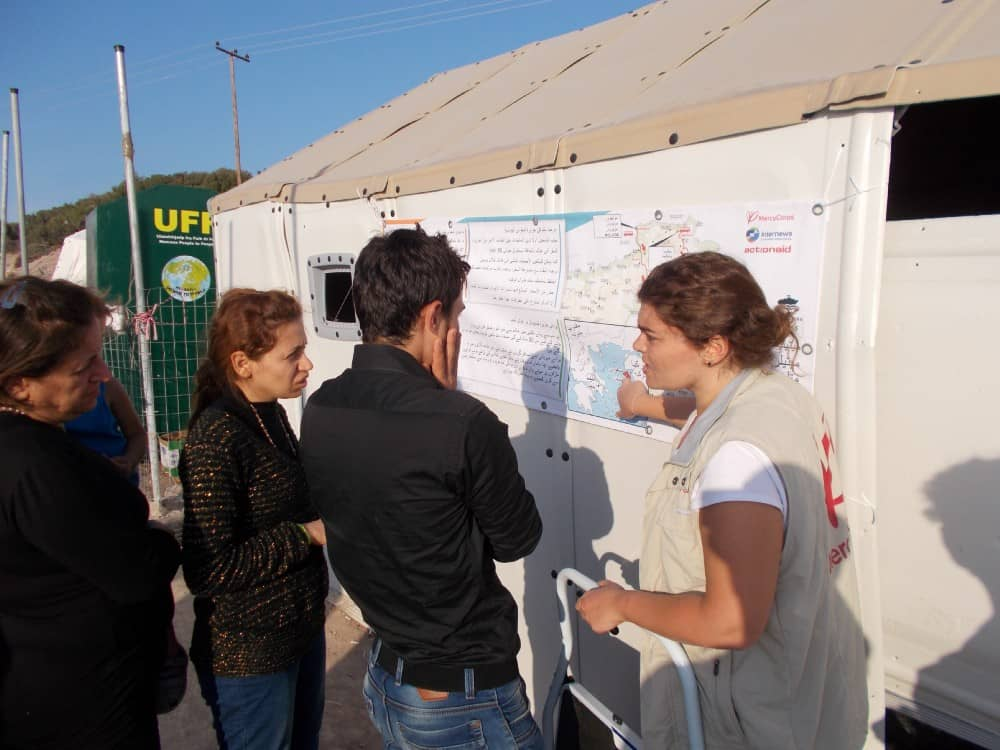 An aid worker points to a map on a banner while 3 refugees look on
