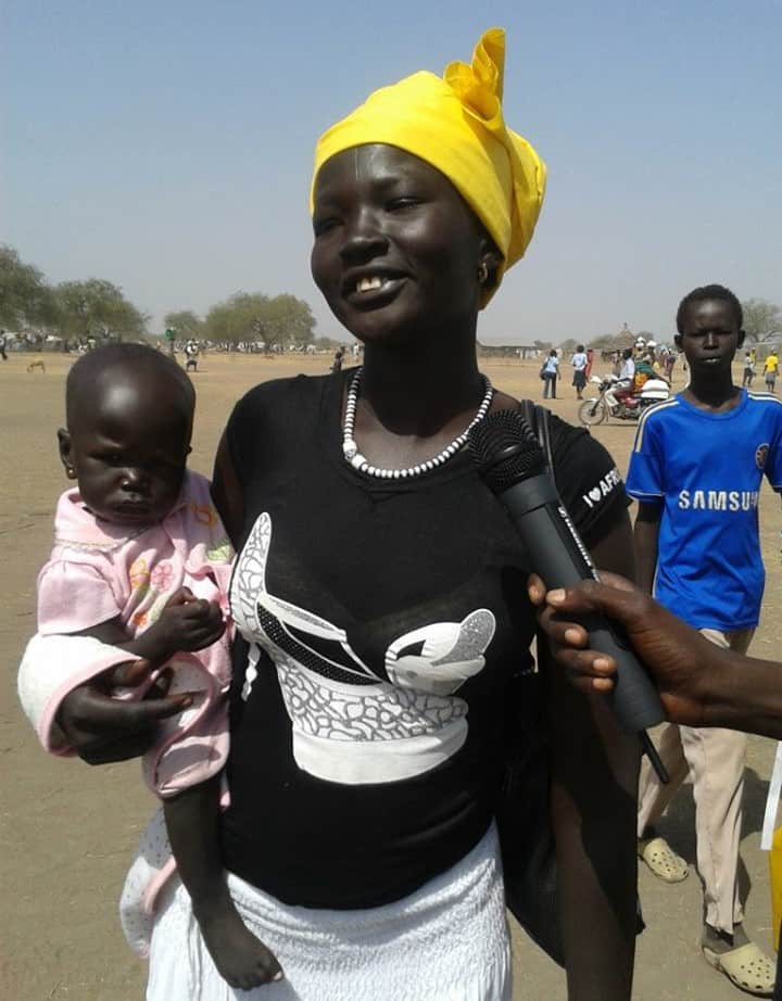 A woman stands outside in the heat holding her baby