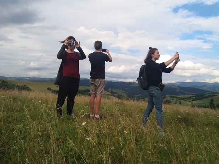 Two young women and one man stand on a grassy hill taking photos.