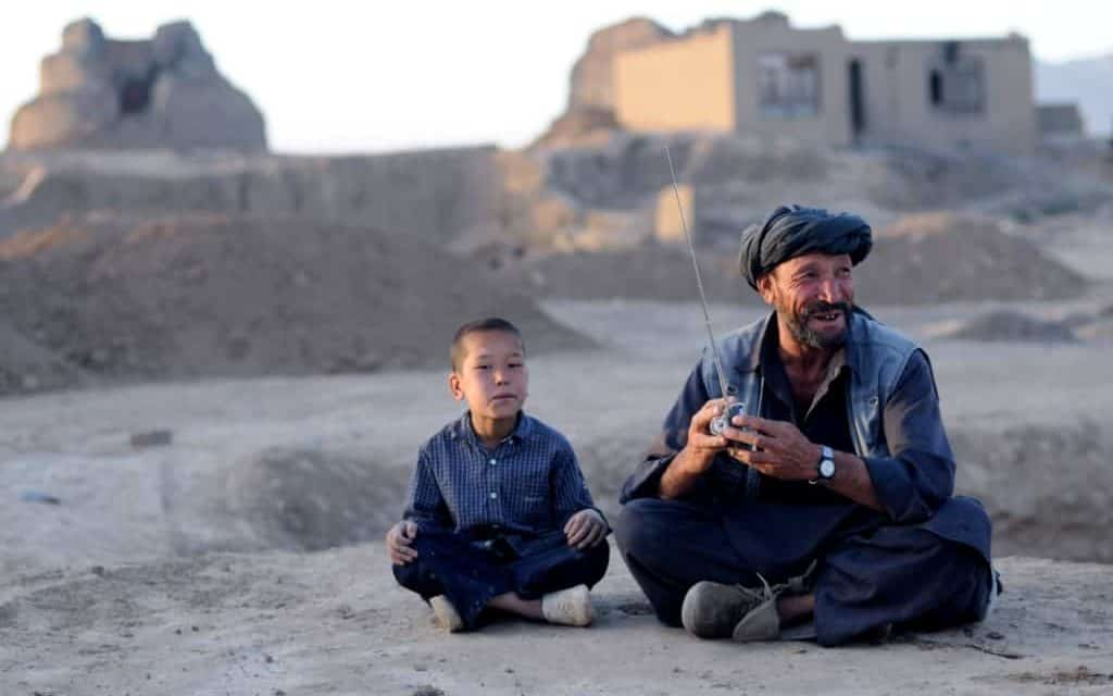 A man holding a radio and a young boy sit together on the sand - there are some brick buildings behind them