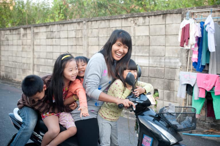 A woman on her motorbike with four children. They are laughing.