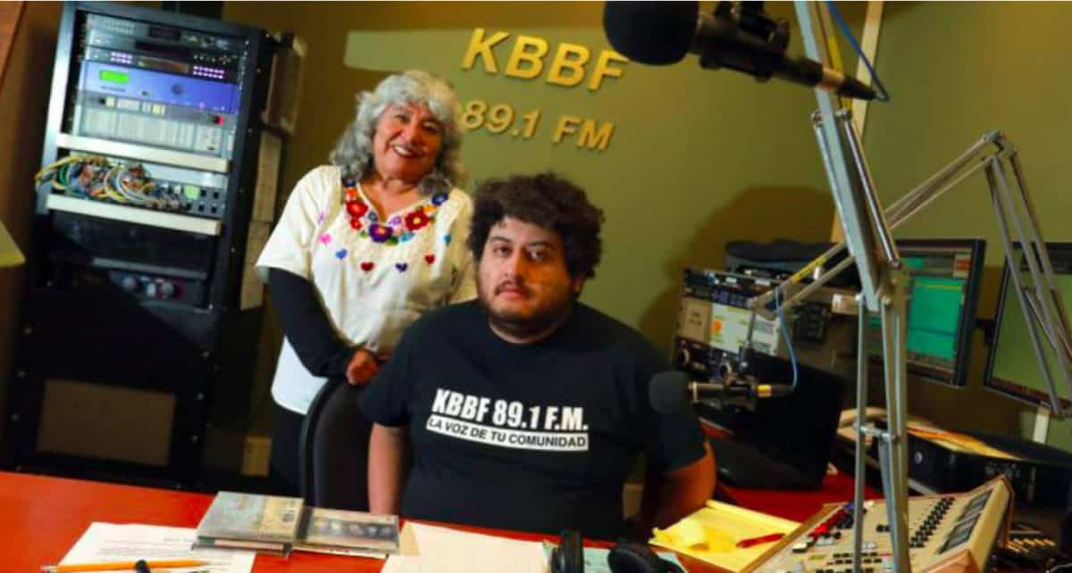 """A man sits at a table with an older woman standing behind him. """"KBBF 89.1 FM"""" is on the wall behind them."""