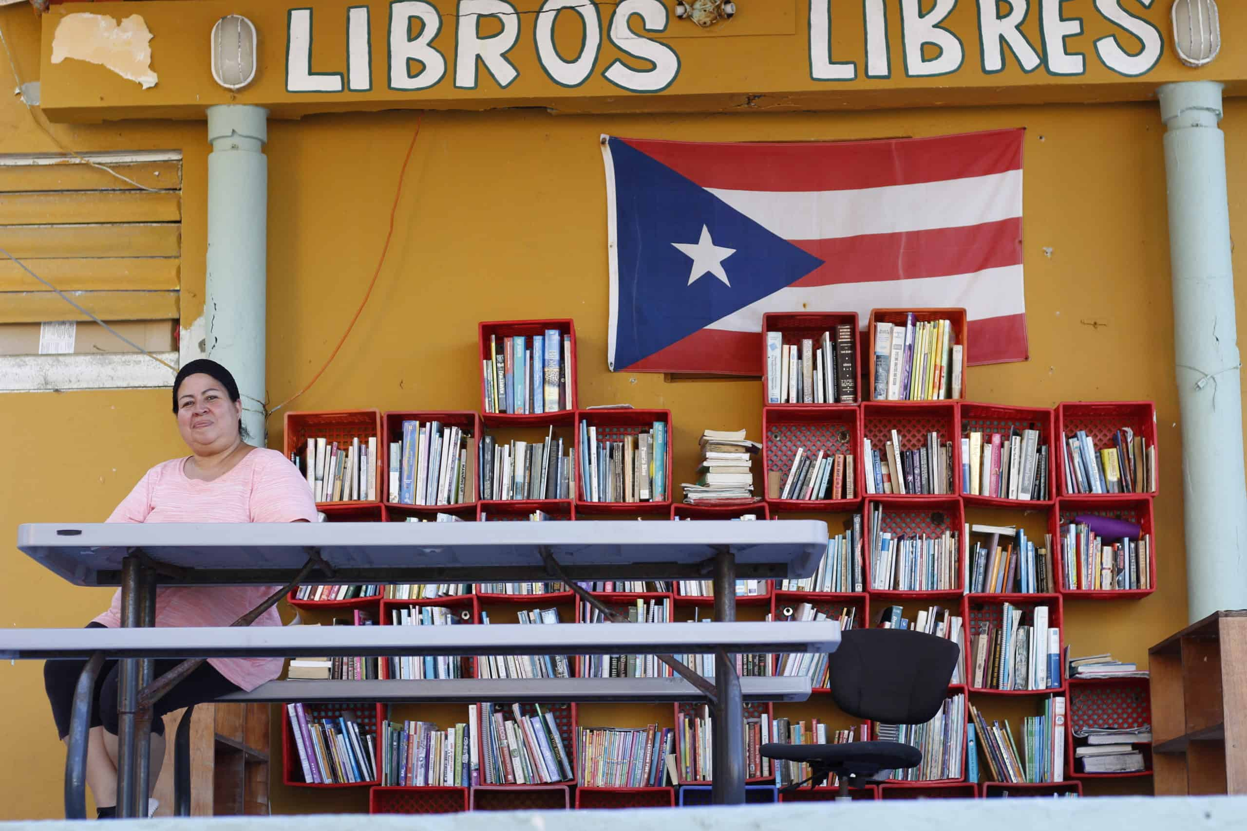 A woman sits at a picnic table in front of bookshelves filled with books and a Puerto Rican flag.