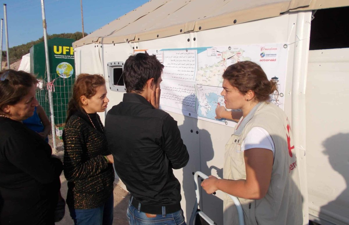 A woman points to a large map posted on the side of a tent