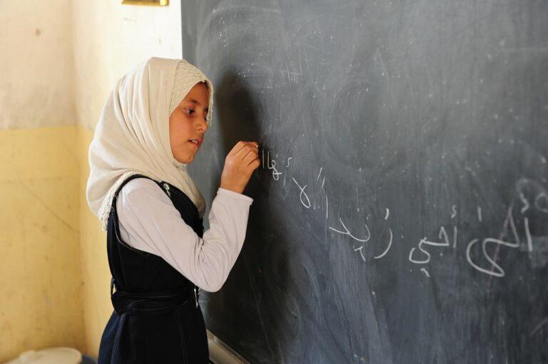 A girl writes on a blackboard.