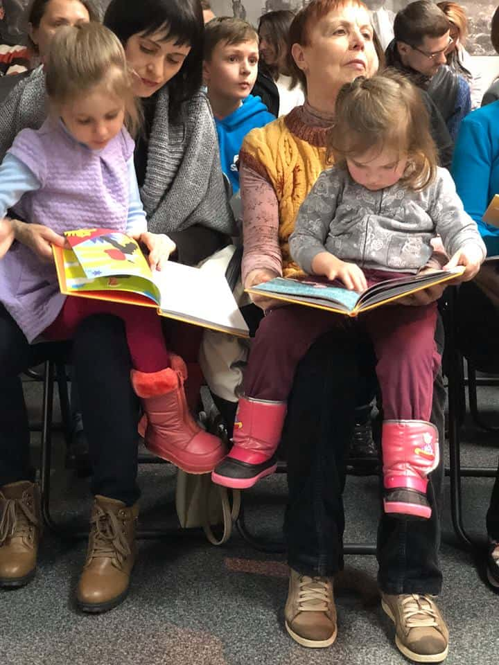 Two girls holding books sit on their mothers' laps