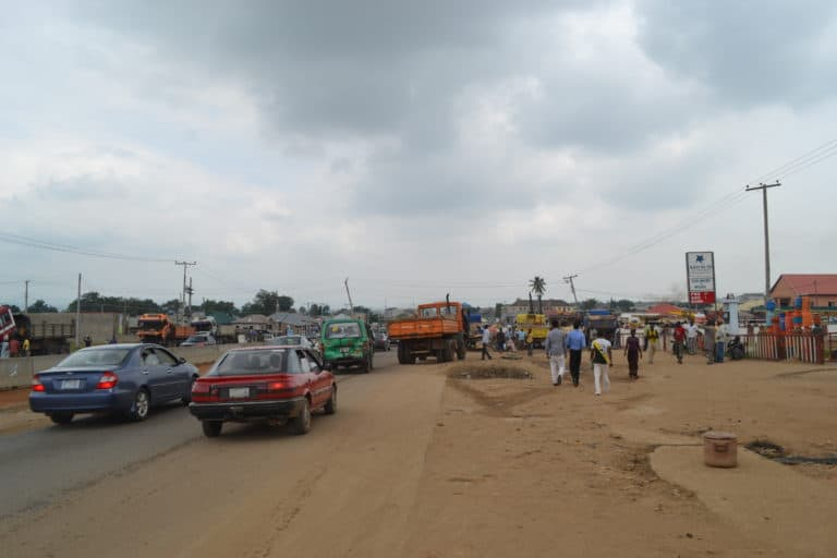 Cars, trucks and people on a dirt road in a commercial district.