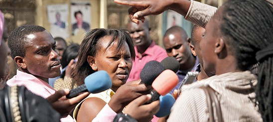 Several men and a woman hold up mics to a woman who is speaking.