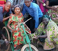 A woman sits on a wheelchair bike while another woman squats next to her, two men stand behind.