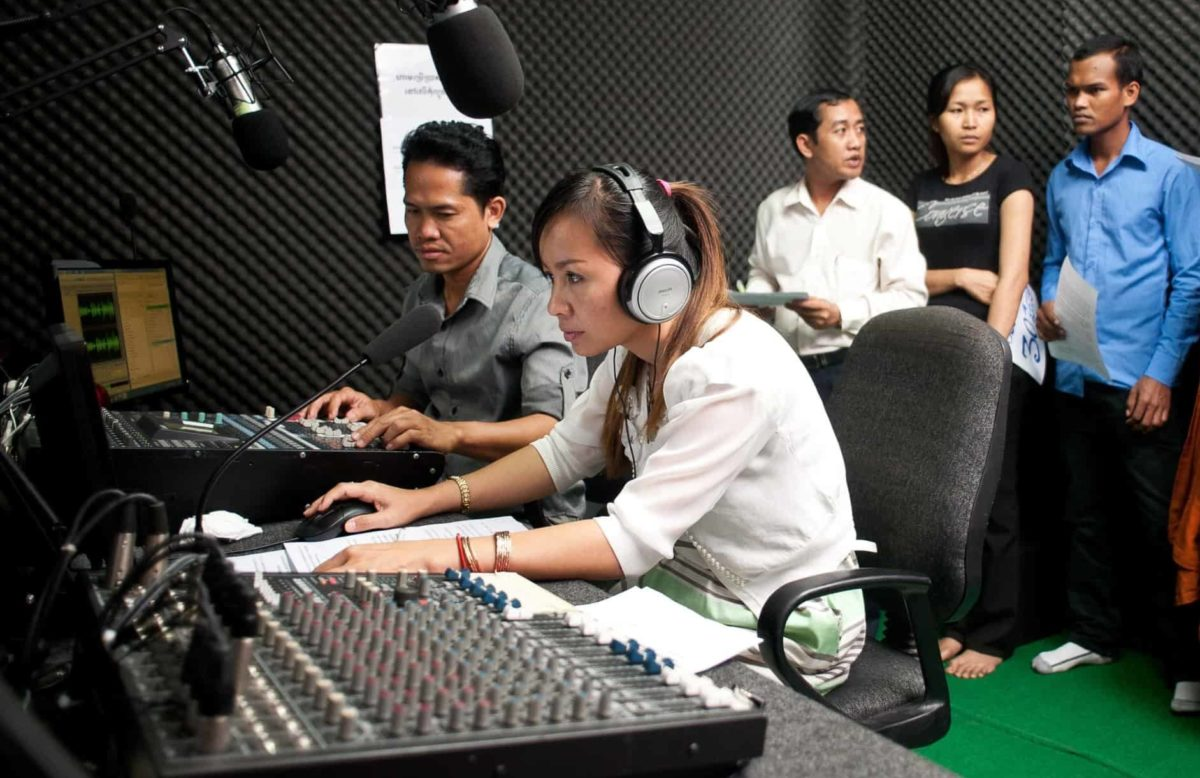 A group of people gather in a radio studio