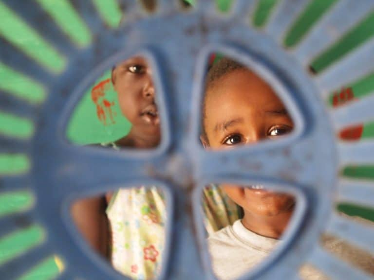 Two children look through a plastic structure.