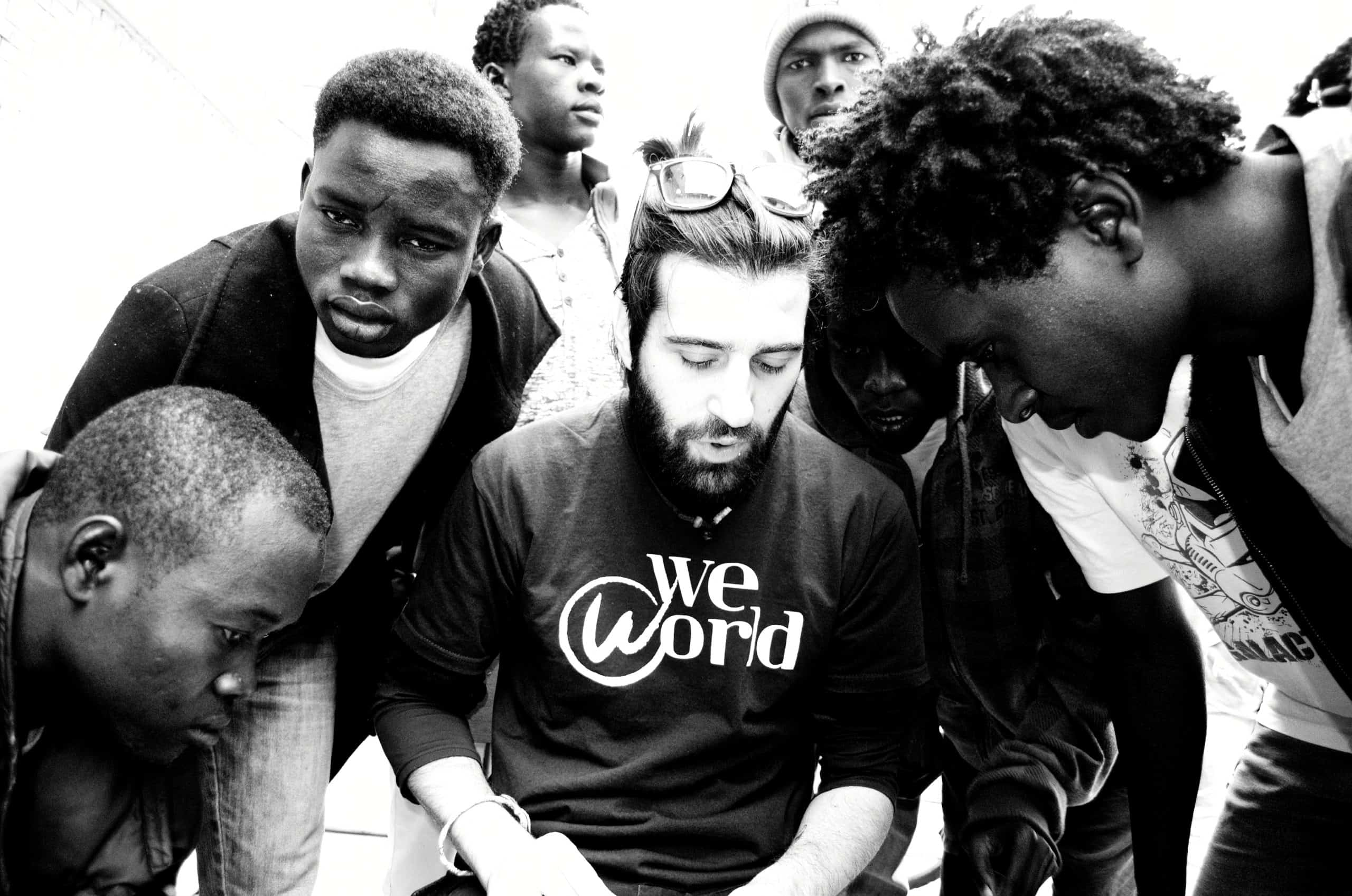 A white man with a beard sits. A group of young black men stand around him.