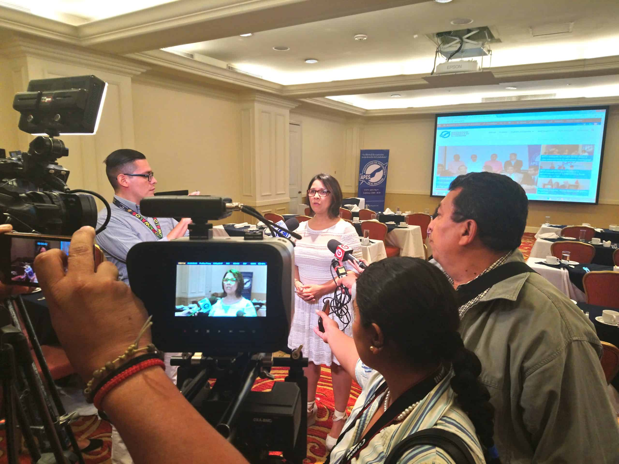A group of journalists interviews a woman (Dalila Arriaza) using video cameras and microphones.